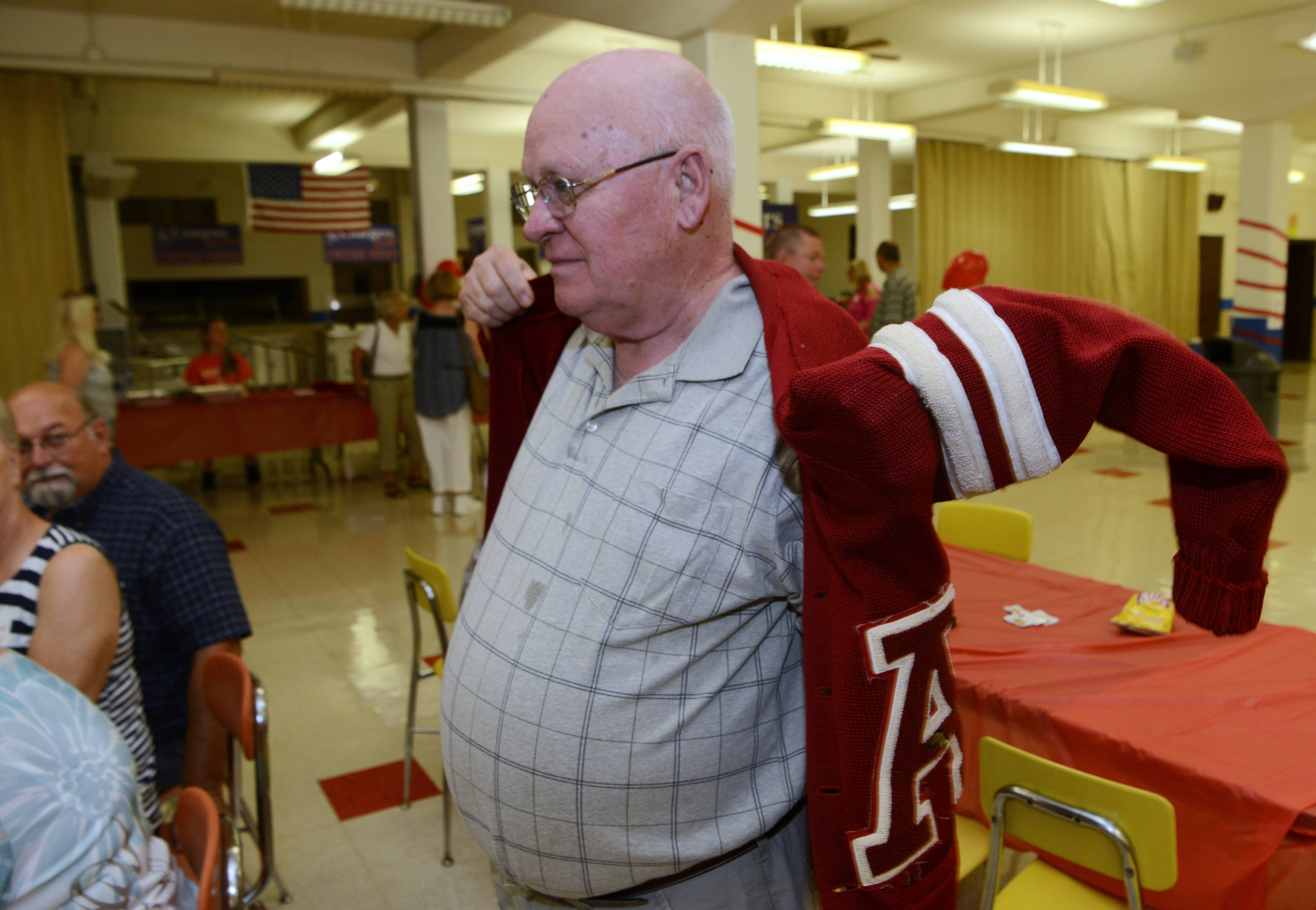 Mike East of the class of 1964 puts on his varsity sweater during the Arlington High School all-class homecoming, held at the former school building, which is now Christian Liberty Academy, in Arlington Heights Saturday.