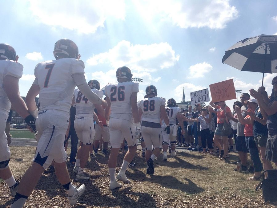 Wheaton College football fans cheer for players as they run onto the field to play Elmhurst College in the first game since hazing charges were announced against five players.