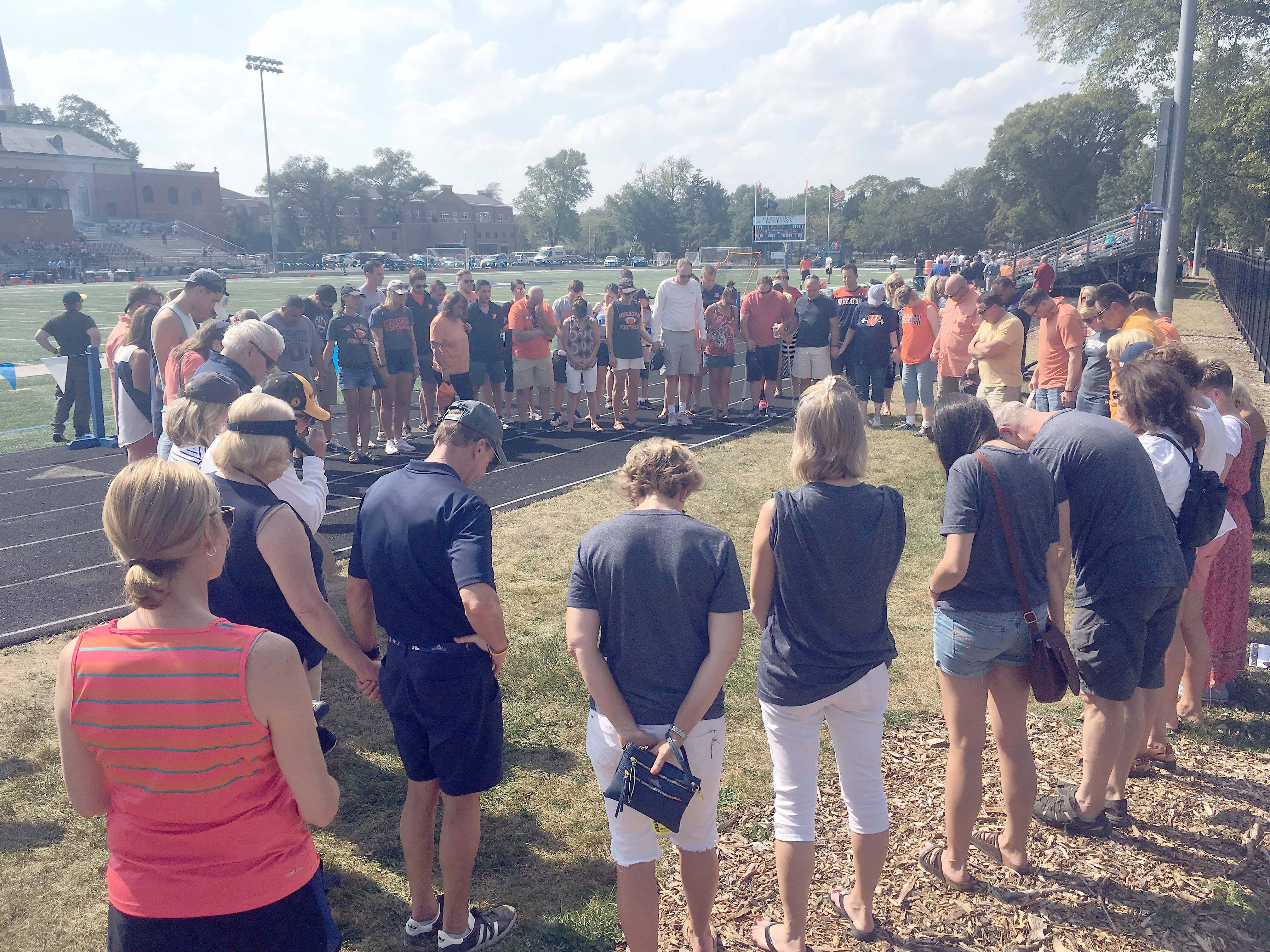 Wheaton College fans pray before a football game Saturday at Elmhurst College, the first since charges against five players in connection to a hazing incident.