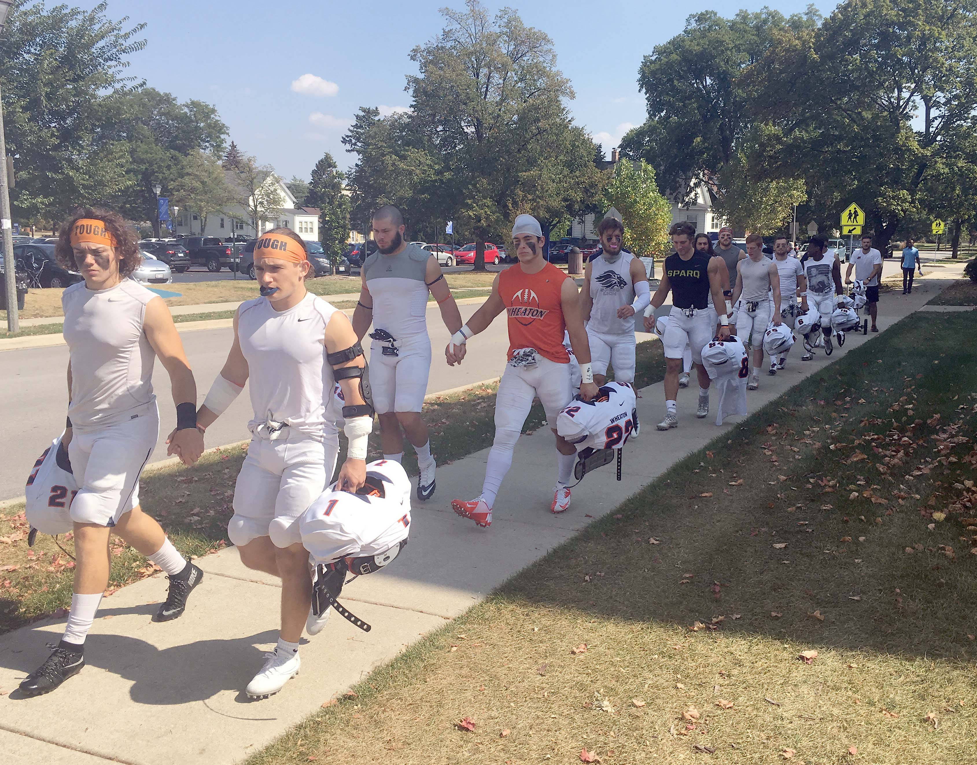Wheaton College football players join hands as the walk to the field to play Elmhurst College in the first game since hazing charges were announced against five players.