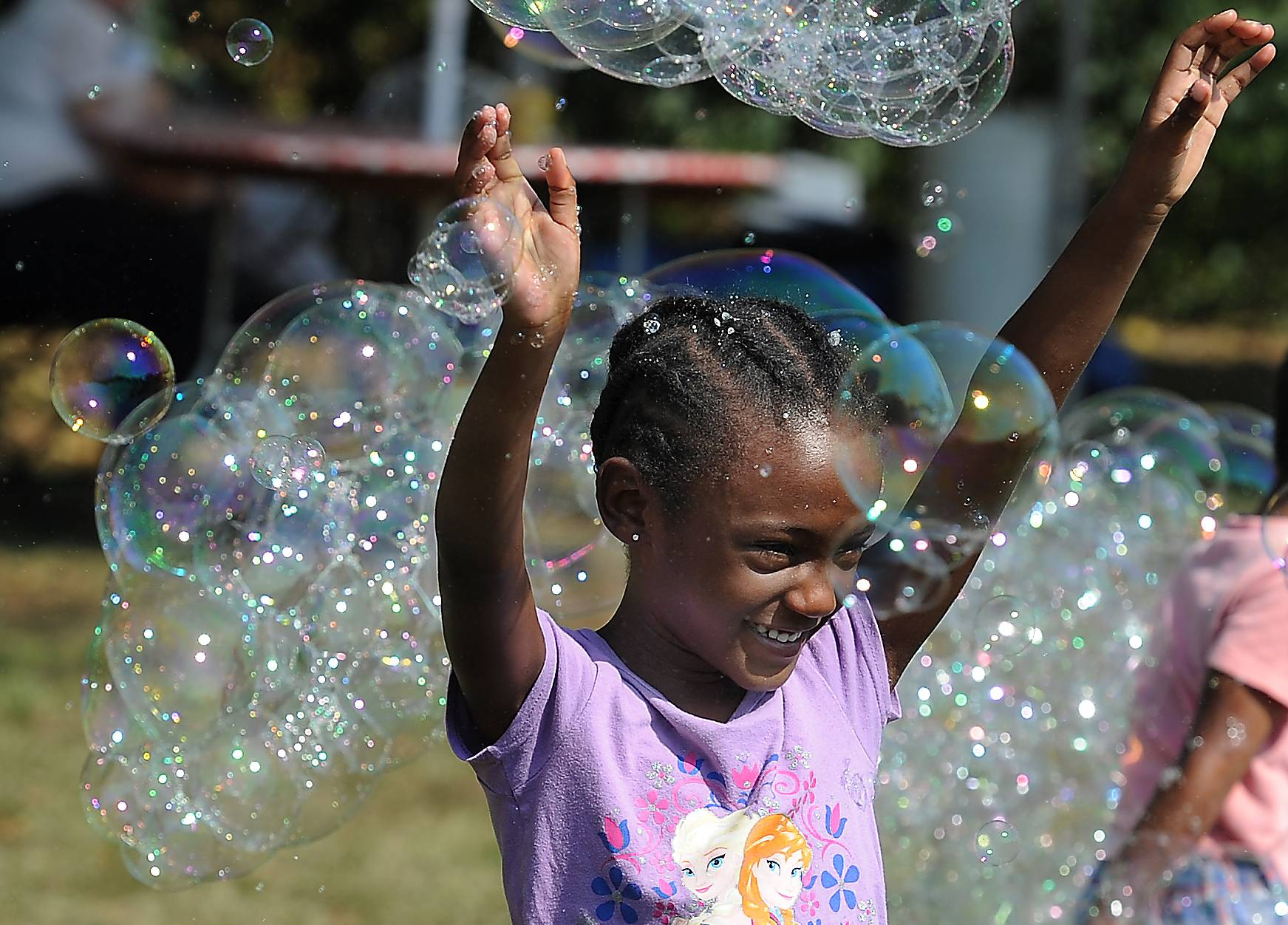 Aaliyah Siggers, 5, of Berwyn plays in the bubbles produced by Gordy Tobutt of Fox River Grove, also called The Bubbler, at the Long Grove Apple Fest on Saturday.