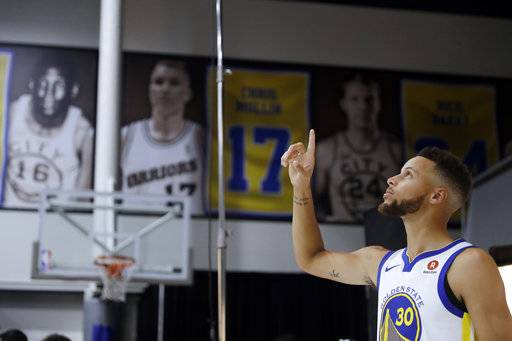 Golden State Warriors' Stephen Curry poses for photos during NBA basketball team media day Friday, Sept. 22, 2017, in Oakland, Calif.