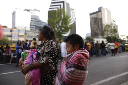 People stand in the street after hearing an earthquake alarm, in Mexico City, Saturday, Sept. 23, 2017. A strong aftershock rolled through Mexico City, Saturday morning, swaying buildings and sending some people running into the street. (AP Photo/Natacha Pisarenko)