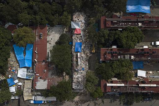 An aereal the view of remains of the Unidad Habitacional Tlalpan 1-C building in the Conjunto Urbano Tlalpan neighborhood of Mexico City, on Saturday, Sept. 23, 2017. A strong new earthquake shook Mexico on Saturday morning, causing street signs around the collapsed building to sway and rescue workers to evacuate the site temporarily.