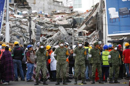 CORRECTS TO CLARIFY SITUATION WAS AN EVACUATION - Rescue workers and volunteers stand in the middle of the street after an earthquake alarm sounded and a small tremor was felt during rescue operations at the site of a collapsed building in Roma Norte, in Mexico City, Saturday, Sept. 23, 2017. All rescue workers atop the rubble were able to evacuate safely via an adjacent building.