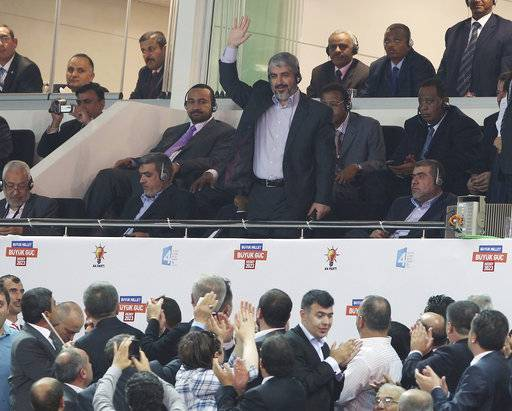 FILE - In this Sept. 30, 2012 file photo, Palestinian Hamas leader Khaled Mashaal salutes cheering members of Turkish Prime Minister Recep Tayyip Erdogan's Justice and Development Party, the AKP, during the congress of AKP in Ankara, Turkey. Iran tries to reconcile Syria and Hamas, rebuilding alliance. The reconciliation attempt comes after Hamas elected a new leadership and as its main backers, Qatar and Turkey, both strong supporters of the rebels in Syria, have sought to improve relations with Iran. (AP Photo, File)