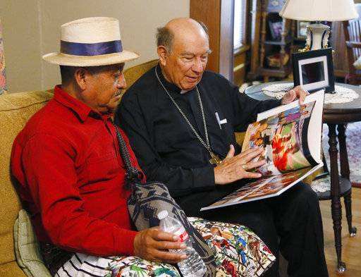 Guatemalan Bishop Julio Edgar Cabrera, right, looks over a Rother Family photo book with Juan Pablo Ixbalan, left, at the Rother Family home in Okarche, Okla, Thursday, Sept. 21, 2017. Stanley Rother, an American priest killed during Guatemala's civil war, is on the path to possible sainthood. Ixbalan knew Rother during his time in Guatemala. A ceremony for Rother's Beatification is scheduled for Saturday, Sept. 23, 2017.