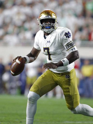 Notre Dame quarterback Brandon Wimbush rolls out before throwing a touchdown pass against Michigan State during the second quarter of an NCAA college football game, Saturday, Sept. 23, 2017, in East Lansing, Mich.