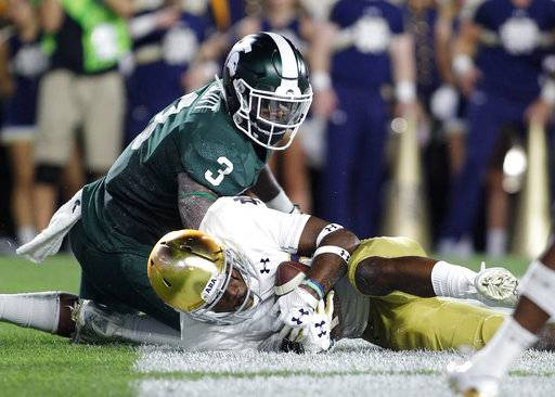 Notre Dame's Shaun Crawford, bottom, recovers a fumble in the end zone for a touchback after stripping the ball from Michigan State's LJ Scott (3) during the second quarter of an NCAA college football game, Saturday, Sept. 23, 2017, in East Lansing, Mich.