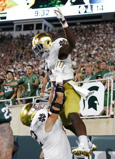 Notre Dame's Dexter Williams is lifted by Robert Hainsey as they celebrate Williams' receiving touchdown against Michigan State during the second quarter of an NCAA college football game, Saturday, Sept. 23, 2017, in East Lansing, Mich.