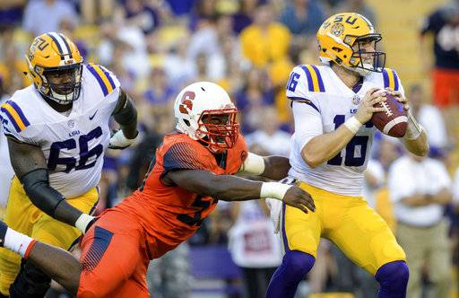 LSU quarterback Danny Etling (16) is sacked by Syracuse defensive lineman Kendall Coleman (55) during the first half of an NCAA college football game in Baton Rouge, La., Saturday, Sept. 23, 2017. (AP Photo/Matthew Hinton)