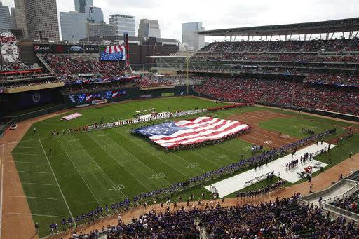 Fans watch as a giant U.S. flag is unfurled on the field for the national anthem before an NCAA college football game between St. John's and St. Thomas on Saturday, Sept. 23, 2017, in Minneapolis. (Anthony Souffle/Star Tribune via AP)