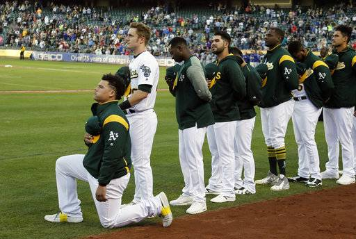Oakland Athletics catcher Bruce Maxwell kneels during the national anthem before the start of a baseball game against the Texas Rangers Saturday, Sept. 23, 2017, in Oakland, Calif. Bruce Maxwell of the Oakland Athletics has become the first major league baseball player to kneel during the national anthem.