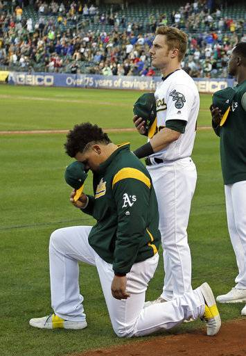 Oakland Athletics catcher Bruce Maxwell, left, kneels as teammate Mark Canha, right, looks on during the National Anthem before the start of a baseball game against the Texas Rangers Saturday, Sept. 23, 2017, in Oakland, Calif. Bruce Maxwell of the Oakland Athletics has become the first major league baseball player to kneel during the national anthem.