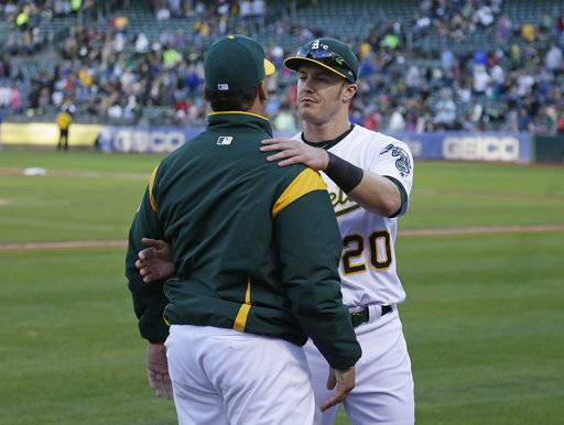 Oakland Athletics catcher Bruce Maxwell, left, is embraced by teammate Mark Canha, right, after Maxwell knelt for the national anthem before the start of a baseball game against the Texas Rangers Saturday, Sept. 23, 2017, in Oakland, Calif.