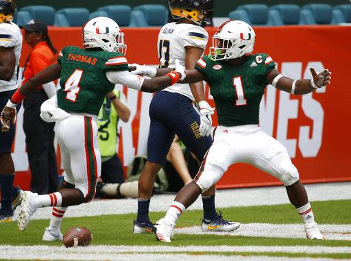 Miami wide receiver Jeff Thomas (4) congratulates running back Mark Walton (1) after Walton ran for a touch down during the first half of an NCAA College football game against Toledo, Saturday, Sept. 23, 2017 in Miami Gardens, Fla. (AP Photo/Wilfredo Lee)