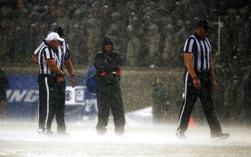Members of an NCAA referee crew stand in a downpour during the first half of an NCAA college football game between Air Force and San Diego State, Saturday, Sept. 23, 2017, at Air Force Academy, Colo. (AP Photo/Jack Dempsey)