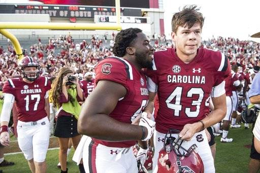 South Carolina place kicker Parker White (43) celebrates with tight end Kiel Pollard, left, after the conclusion of an NCAA college football game against Louisiana Tech Saturday, Sept. 23, 2017, in Columbia, S.C. White hit a game winning field go to lead South Carolina over Louisiana Tech 17-16. (AP Photo/Sean Rayford)