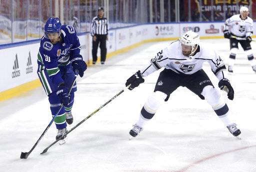 The Vancouver Canucks' Brandon Sutter, left, takes a shot on goal past the Los Angeles Kings' Derek Forbort during the first period of an NHL China exhibition game at the Cadillac Arena in Beijing, Saturday, Sept. 23, 2017.