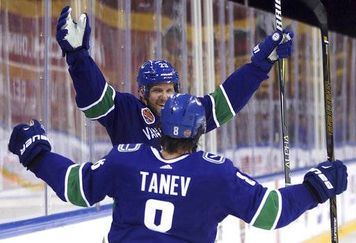 The Vancouver Canucks' Alex Edler celebrates after teammate Chris Tanev, foreground, scored a goal agains the Los Angeles Kings in the third period of their NHL China exhibition game at the Cadillac Arena in Beijing, Saturday, Sept. 23, 2017. The Kings won 4-3 in an overtime shootout.