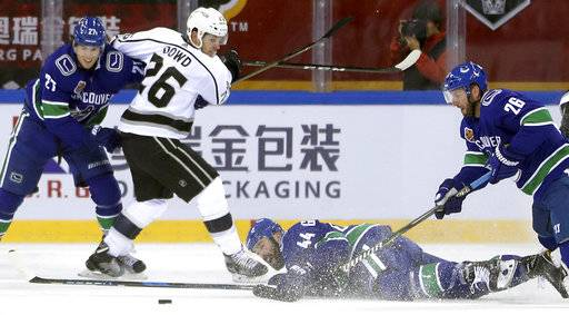 Vancouver Canucks' Erik Gudbranson loses his stick as he falls to the ice while battling for the puck with teammates Ben Hutton, left, and Thomas Vanek and The Los Angeles Kings' Nic Dowd during the second period of their NHL China exhibition hockey game at the Cadillac Arena in Beijing, Saturday, Sept. 23, 2017. The Kings won 4-3 in a shootout.
