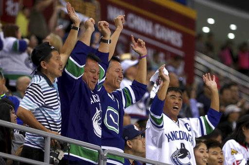 Vancouver Canucks fans cheer after the Canucks' scored a goal against the Los Angeles Kings during the third period of their NHL China exhibition game at the Cadillac Arena in Beijing, Saturday, Sept. 23, 2017. The Kings won 4-3 in an overtime shootout.