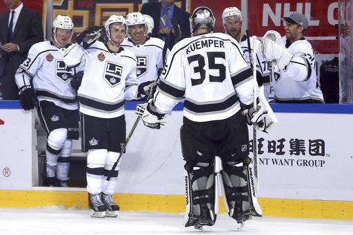 Members of the Los Angeles Kings celebrate with goalie Darcy Kuemper (35) after winning their NHL China exhibition game against the Vancouver Canucks at the Cadillac Arena in Beijing, Saturday, Sept. 23, 2017. The Kings won 4-3 in an overtime shootout.