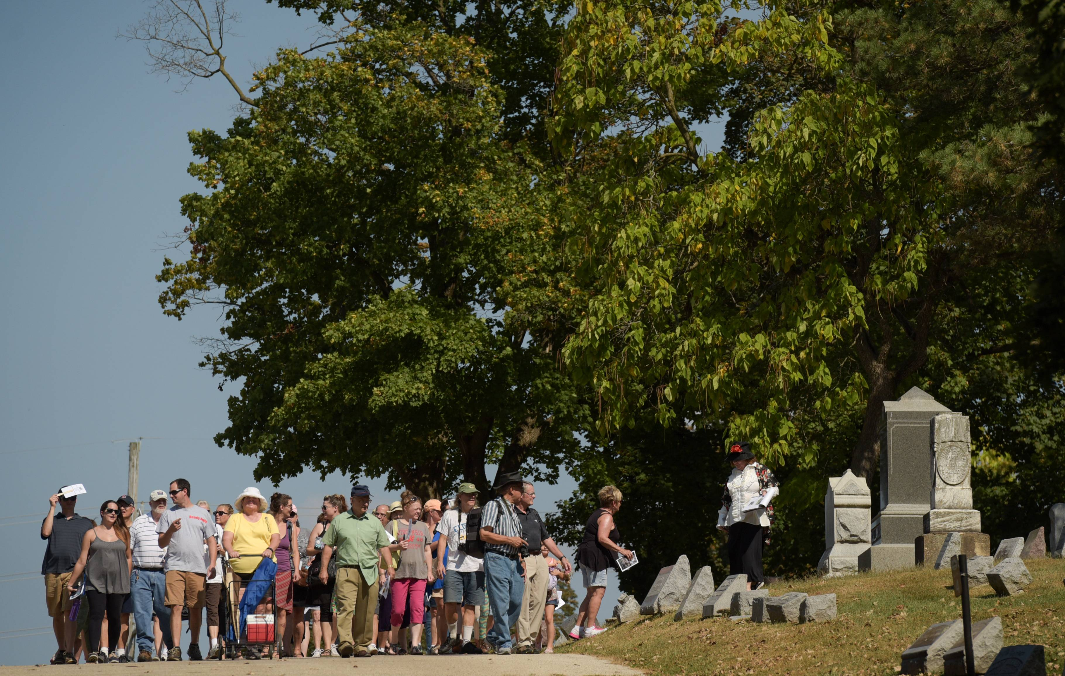 A large group navigates Bluff City Cemetery during the annual Elgin Cemetery Walk Sunday.