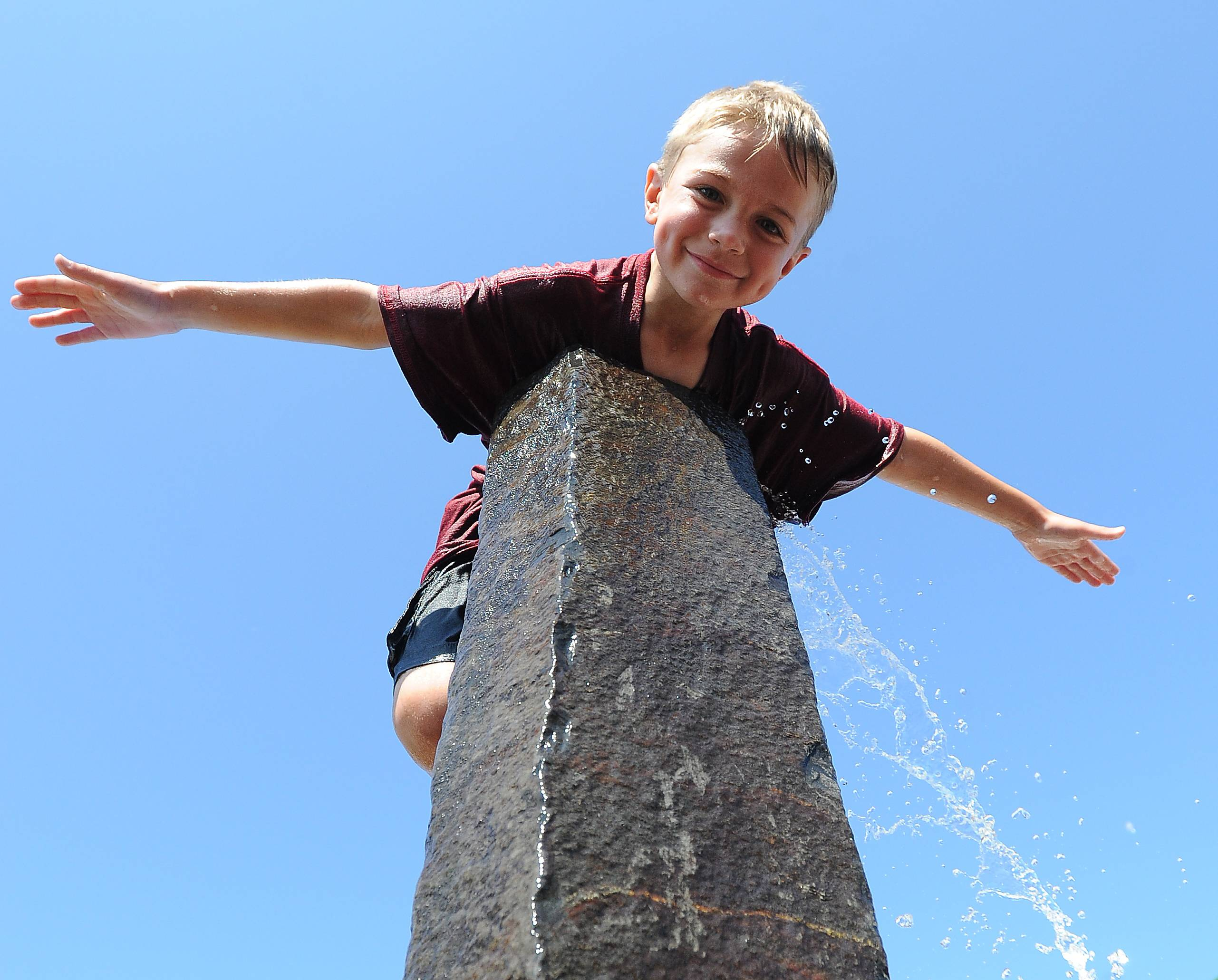 Shane McMillion, 6, of Trevor Wisconsin climbed on top of the water fountain to keep cool as his mom sold goods at the Farm Heritage and Harvest Festival at the Lake County Fairgrounds on Sunday.