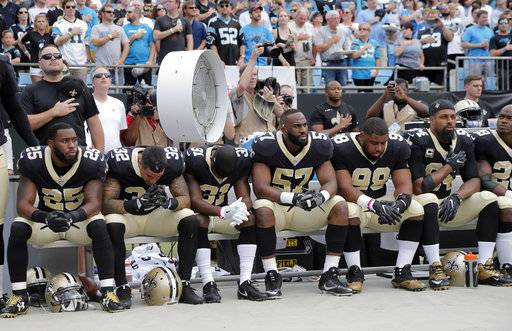 New Orleans Saints players sit on the bench during the national anthem before an NFL football game against the Carolina Panthers in Charlotte, N.C., Sunday, Sept. 24, 2017.
