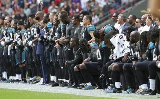 Jacksonville Jaguars players lock arms and kneel down during the playing of the U.S. national anthem before an NFL football game against the Baltimore Ravens at Wembley Stadium in London, Sunday Sept. 24, 2017.
