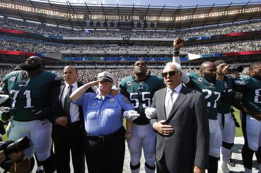 Philadelphia Eagles players, owner Jeffrey Lurie, center right, Eagles' President Don Smolenski, second from left, and a Philadelphia police officer, third from left, stand for the national anthem before an NFL football game against the New York Giants, Sunday, Sept. 24, 2017, in Philadelphia. Eagles' Malcolm Jenkins raises his fist next to Lurie.