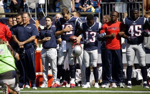New England Patriots head coach Bill Belichick, left, and Tom Brady (12) Phillip Dorsett (13) Matthew Slater, second from right, and David Harris (45) stand during the national anthem before an NFL football game against the Houston Texans, Sunday, Sept. 24, 2017, in Foxborough, Mass.