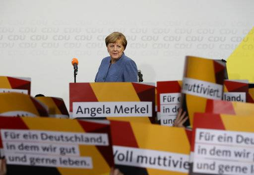 Supporters hold posters as German Chancellor Angela Merkel returns on the stage at the headquarters of the Christian Democratic Union CDU in Berlin, Germany, Sunday, Sept. 24, 2017 after the German parliament election.