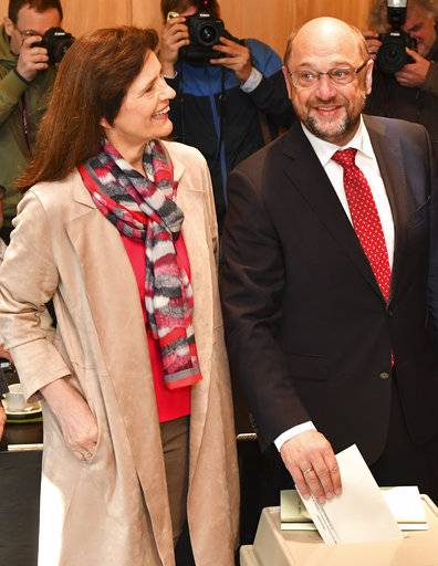Inge Schulz, left, looks to her husband Martin Schulz, top candidate and chairman of the Social Democratic Party, as he casts his vote in the German parliament election in Wuerselen, Germany, Sunday, Sept. 24, 2017. Schulz is challenging Chancellor Angela Merkel who is widely expected to win a fourth term in office as Germans go to the polls.
