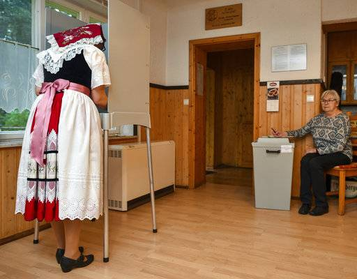 Anita Storch in a traditional Sorbian dress casts her vote in the German parliament election in Lehde, eastern Germany, Sunday, Sept. 24, 2017. Chancellor Angela Merkel is widely expected to win a fourth term in office as Germans go to the polls. (Patrick Pleul/dpa via AP)