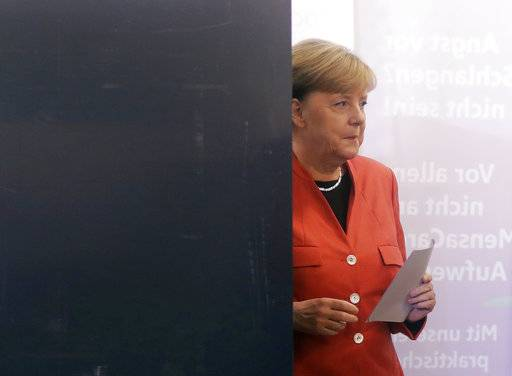 German Chancellor Angela Merkel leaves the election booth as she casts her vote in Berlin, Germany, Sunday, Sept. 24, 2017. Merkel is widely expected to win a fourth term in office as Germans go to the polls to elect a new parliament.