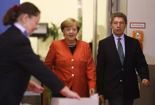 German Chancellor Angela Merkel, center, and her husband Joachim Sauer arrive to cast their votes in Berlin, Germany, Sunday, Sept. 24, 2017. Merkel is widely expected to win a fourth term in office as Germans go to the polls to elect a new parliament.