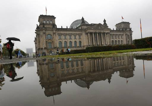 CORRECTS ORIENTATION OF THE IMAGE - The Reichstag building which hosts the German parliament is mirrored in a puddle in Berlin, Germany, Sunday, Sept. 24, 2017, when Germans election a new parliament.