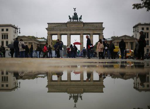 CORRECTS ORIENTATION OF THE IMAGE - The Brandenburg Gate is mirrored in a puddle in Berlin, Germany, Sunday, Sept. 24, 2017.