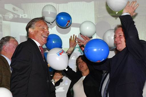 Armin-Paul Hampel, second left, board member, celebrates with Alexander Gauland, co-top candidate of the nationalist German AfD, 'Alternative for Germany', far left, during the election party in Berlin, Germany, Sunday, Sept. 24, 2017, after the polling stations for the German parliament elections had been closed.