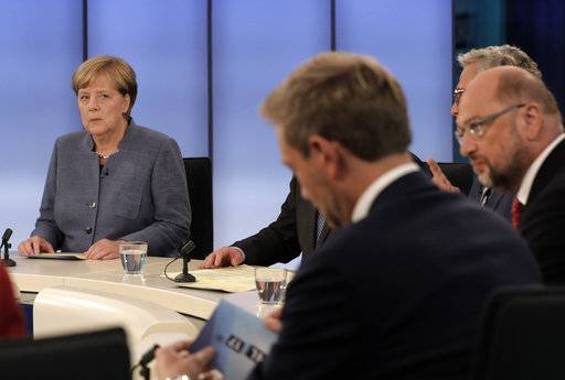 German Chancellor Angela Merkel, head of the Christian Democratic Party CDU, looks to her challenger Martin Schulz, head of the Social Democratic Party SPD, right, and Christian Lindner, head of the Free Democratic Party FDP, front, prior to a TV talk of the party leader in Berlin, Germany, Sunday, Sept. 24, 2017, after the German parliament elections.
