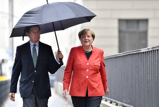 German Chancellor Angela Merkel, right, and her husband Joachim Sauer arrive to cast their vote in Berlin, Germany, Sunday, Sept. 24, 2017. Merkel is widely expected to win a fourth term in office as Germans go to the polls to elect a new parliament.