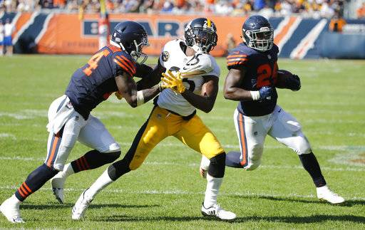 Chicago Bears running back Jordan Howard (24) runs to the end zone for a touchdown in overtime of an NFL football game, Sunday, Sept. 24, 2017, in Chicago. Bears receiver Deonte Thomspon (14) blocks Pittsburgh Steelers cornerback Artie Burns (25) on the play. The Bears won 23-17 in overtime.