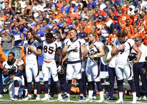 Denver Broncos tight end Virgil Green (85) gestures as teammate Max Garcia, left, takes a knee during the playing of the national anthem prior to an NFL football game against the Buffalo Bills, Sunday, Sept. 24, 2017, in Orchard Park, N.Y.
