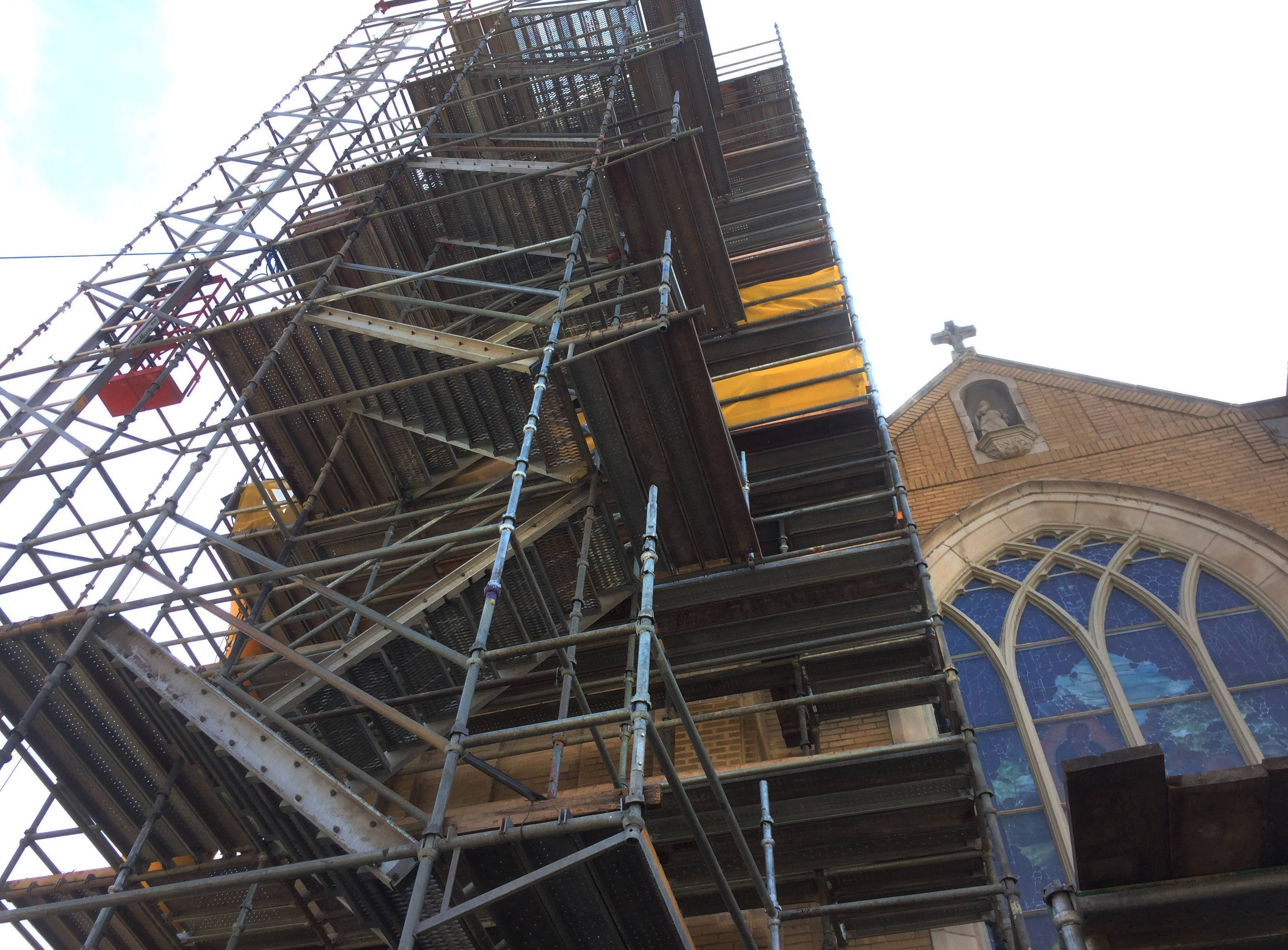 The scaffolding at St. Peter Church in Volo extends high as a crew works to repair the brick and restore the original bell tower and spire which was removed after being damaged by lightning in 1961.