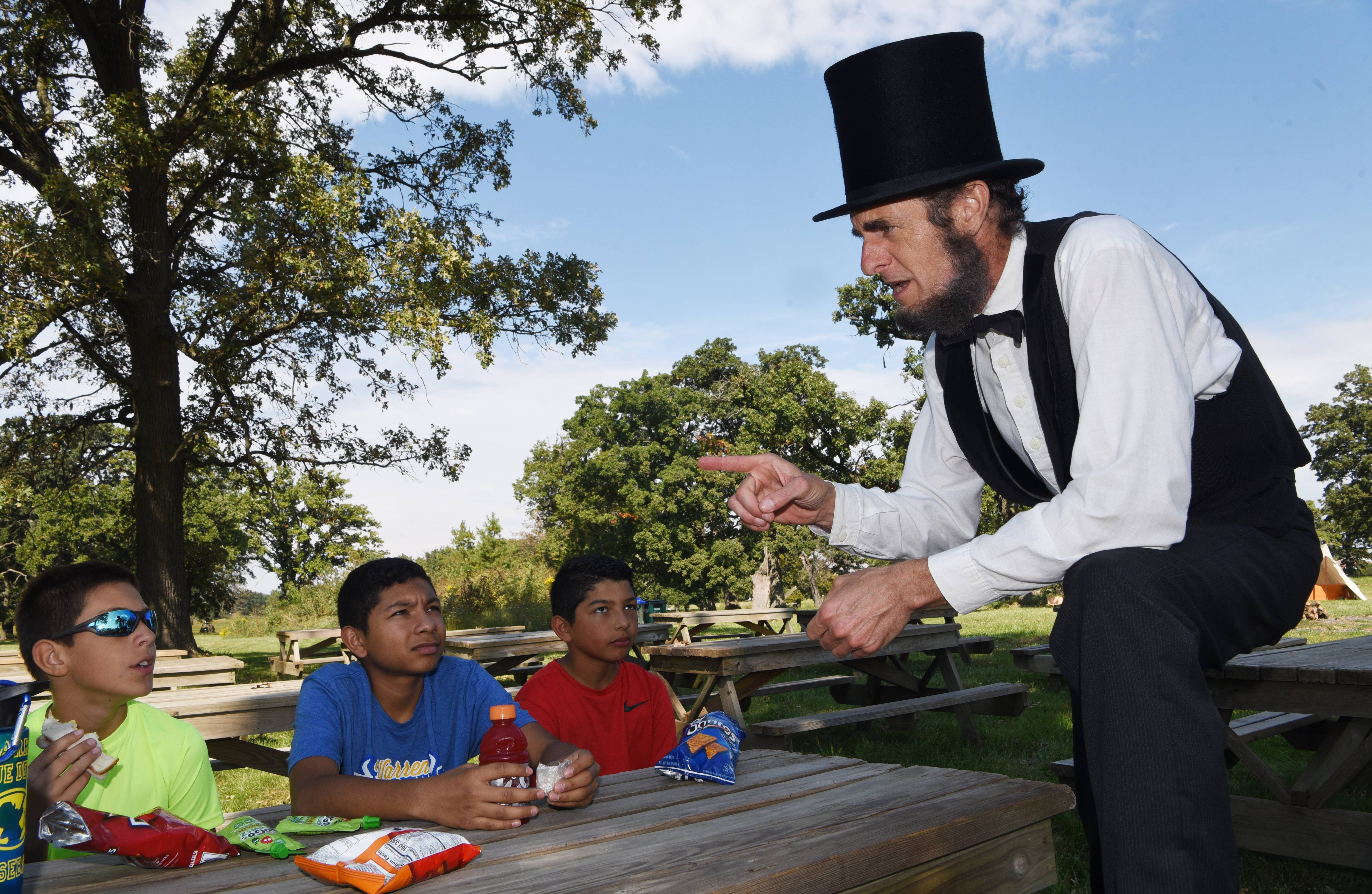 President Abraham Lincoln, portrayed by Kevin Wood of Oak Park, visits with Jake Jurkacek, 11, left, of Round Lake Park and Jacob Rolon, 13, of Round Lake Beach and his brother, Javier, 10, as they have lunch in the picnic grove during a Civil War reenactment in Hainesville Sunday.