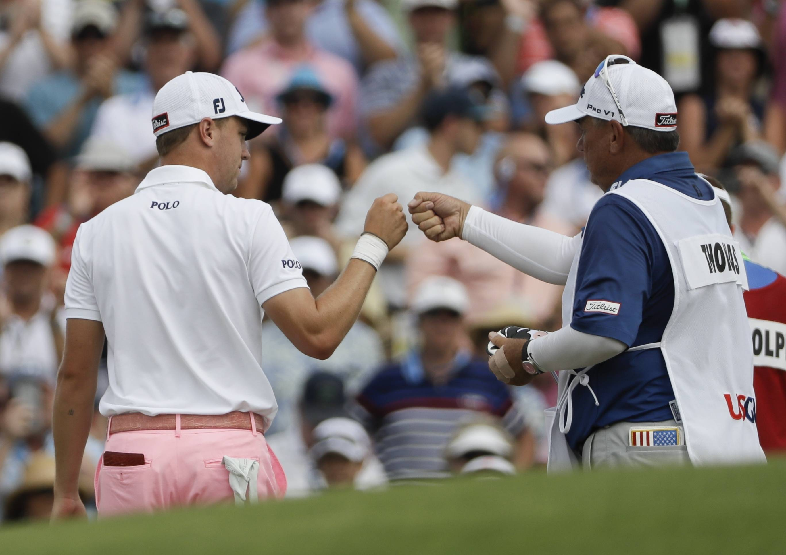 Justin Thomas is congratulated by his caddie after his eagle on the 18th hole during the third round of the U.S. Open at Erin Hills in Erin, Wisconsin.