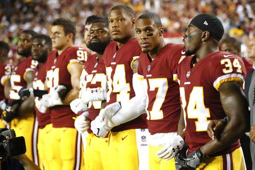Member of the Washington Redskins stand arm in arm during the playing of the National Anthem before an NFL football game against the Oakland Raiders in Landover, Md., Sunday, Sept. 24, 2017. (AP Photo/Pablo Martinez Monsivais) The Associated Press