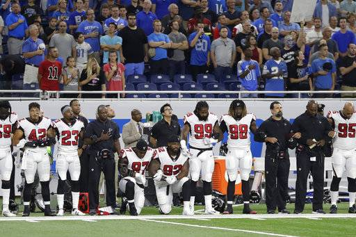 Atlanta Falcons defensive tackles Grady Jarrett (97) and Dontari Poe (92) take a knee during the national anthem before an NFL football game, Sunday, Sept. 24, 2017, in Detroit. (AP Photo/Carlos Osorio)The Associated Press